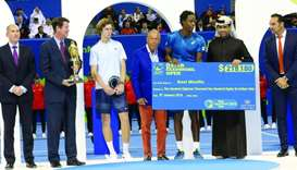 Gael Monfils receives the winner's cheque from Qatar Tennis Federation President Nasser bin Ghanim a