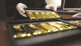An employee displays one-kilogram gold bars at a store in Tokyo. Citing data published by the World