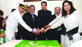 The ambassador and officers of the Pakistan embassy cutting the cake.