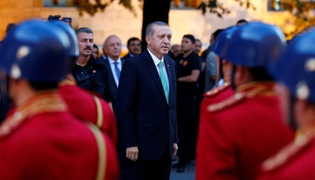Turkish President Tayyip Erdogan reviews a guard of honour as he arrives to the Turkish Parliament i