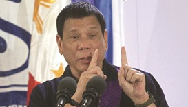 President Rodrigo Duterte gestures while delivering a speech before female police officers during a