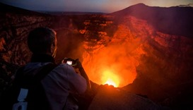 A tourist takes pictures of a lava lake inside the crater of the Masaya Volcano in Masaya
