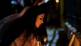 A Bahraini woman lights a candle during a vigil outside the French embassy in Manama