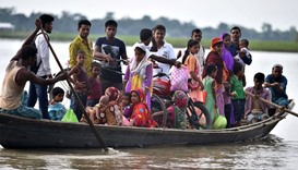 Indian villagers travel by boat over floodwaters in Ashigarh village in the Morigoan district of Ass