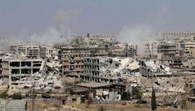 Smoke billows from buildings during an operation by Syrian government forces on the northwest outski