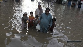 A family wade through the flood waters following a heavy rain in Lahore, Pakistan