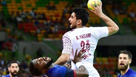 France's right wing Luc Abalo (L) challenges Qatar's left wing Kamal Aldin Mallash