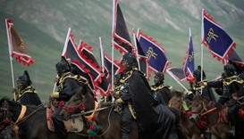 Ethnic Tibetans in traditional dress ride horses whilst holding flags