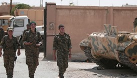 Kurdish fighters from the People's Protection Units (YPG) walk in the Ghwairan neighborhood of Hasak