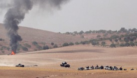 Turkish army tanks and Turkish-backed Syrian fighters make their way in the Syrian border town of Ja