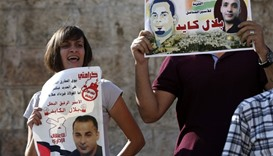 Palestinian protestors hold posters during a demonstration against administrative detention and in s