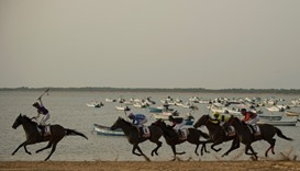 Jockeys race along the beach during the race
