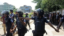Bangladesh police stand guard at the scene of an operation to storm a militant hideout in Narayangan