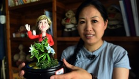Wu Xiaoli holding a dough figurine of German Chancellor Angela Merkel