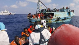 Italian coast guard personnel taking part in a rescue operation of a boat with migrants