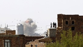 Yemenis stand on a rooftop looking at smoke billowing from a building following a reported air strik