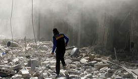 A man walks on the rubble of damaged buildings at al-Qaterji neighbourhood of Aleppo