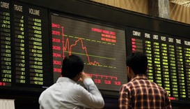 Brokers look at digital screen during bearish trend at a Stock Exchange