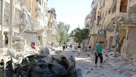 People inspect the damage at a site hit overnight by an air strike in the rebel-held area of Seif al