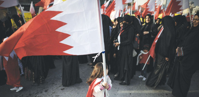 A girl waves her national flag at a demonstration near Manama.