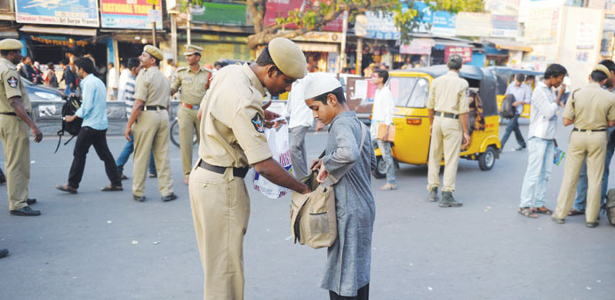 Police check the baggage of a passenger outside a railway station in Secunderabad, the twin city of