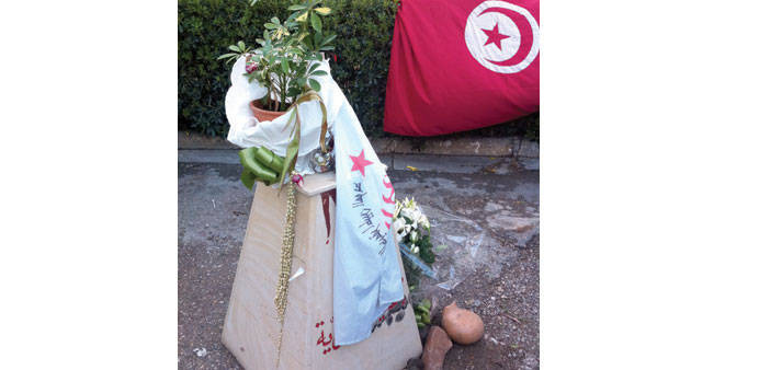 * A potted plant on a knee-high plinth, wrapped in a party flag, marks the spot in Tunis where Chokr