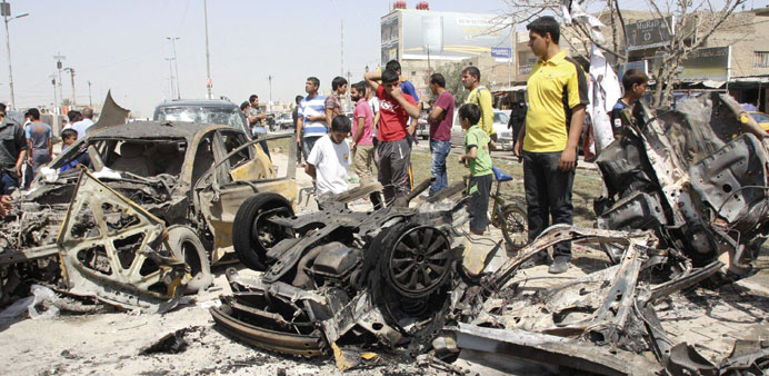 Residents look at wrecked cars at the site of a bomb attack in Sadr City in Baghdad yesterday.