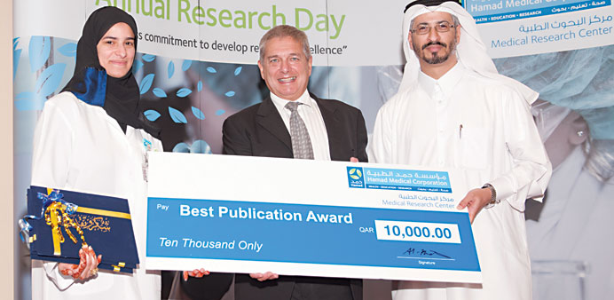 Dr al-Khater presenting a cheque to one of the award winner at the HMC Second Annual Research Day ev