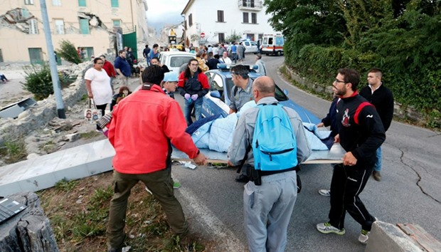 People stand along the road following a quake in Amatrice, central Italy