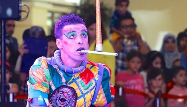 A performer entertains spectators with his balancing act