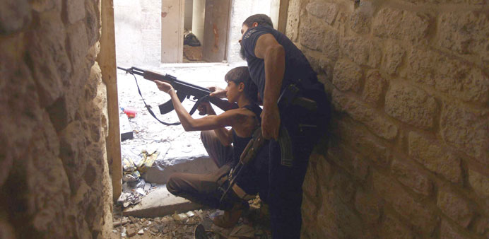 Ahmed Abu Layl, a 15-year-old fighter from the Free Syrian Army, aims his weapon as his father stand