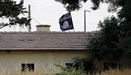 An Islamic State flag flies over the custom office of Syria's Jarablus border gate